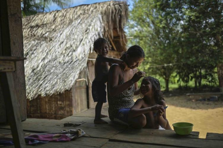 A Timbo Indian mother smiles as she does her six-year-old daughter's hair. Her second son plays behind her. Image by Luis Ángel. Colombia, 2019.