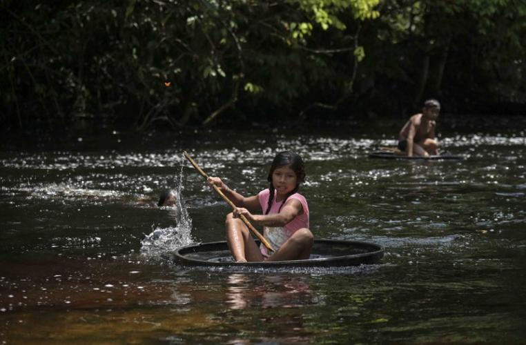 A girl sails on a float, made from a tire, over the stream in the community of Timbó. Image by Luis Ángel. Colombia, 2019.
