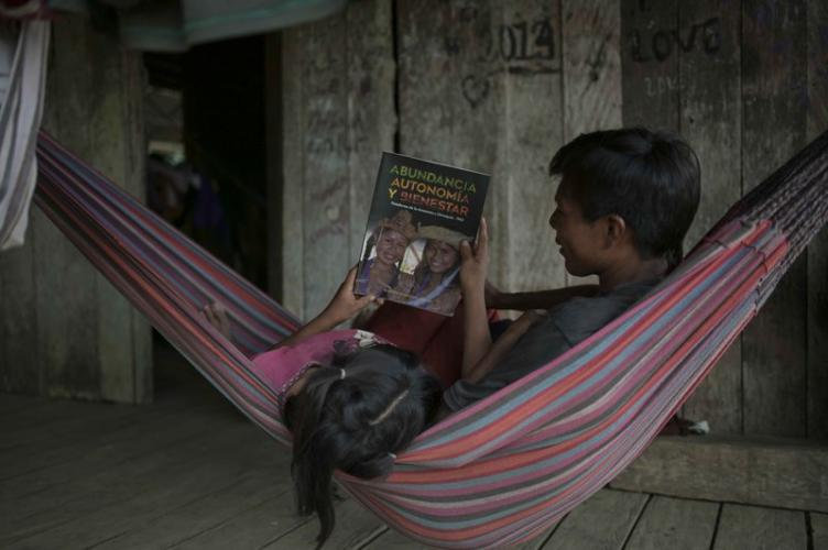 A girl and her father read a magazine about the knowledge and customs of the indigenous peoples. Image by Luis Ángel. Colombia, 2019.