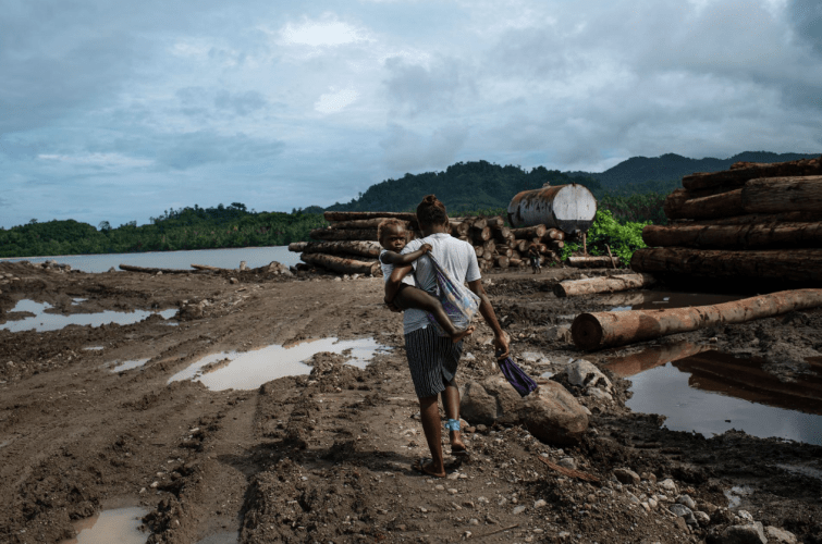 A woman walks through a logging point, used by the Apex company, on the eastern tip of Guadalcanal Island. Logging points like these are crucial for moving round logs to ships, and out of the country. Image by Monique Jaques. Solomon Islands, 2020.